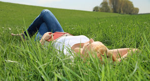 Young woman lying on green meadow Royalty Free Stock Images