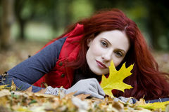 A young woman lying on the ground, holding an autumn leaf royalty free stock images