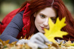 A young woman lying on the ground, looking at an autumn leaf Royalty Free Stock Photo