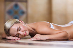 Young woman lying on hammam table in turkish bath Stock Image
