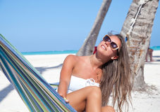 Young woman lying in a hammock on a beach Royalty Free Stock Images