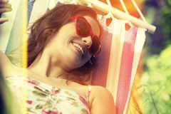 Young woman lying in a hammock in garden. Young woman lying in a hammock in garden on summer Royalty Free Stock Photography