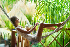 Young woman lying in a hammock with laptop. Young beautiful woman lying in a hammock with laptop in a tropical resort Stock Image
