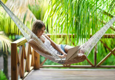 Young woman lying in a hammock with laptop. Young beautiful woman lying in a hammock with laptop in a tropical resort Royalty Free Stock Images