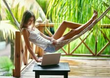 Young woman lying in a hammock with laptop. Young beautiful woman lying in a hammock with laptop in a tropical resort Stock Images