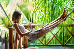 Young woman lying in a hammock with laptop. Young beautiful woman lying in a hammock with laptop in a tropical resort Stock Photo