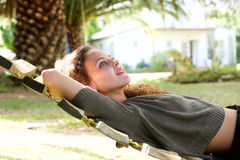 Young woman lying in hammock outside house. Side profile portrait of young woman lying in hammock outside house Stock Image