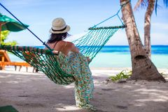Young woman lying in the hammock on tropical beach. Happy young woman lying in the hammock on tropical beach Royalty Free Stock Images
