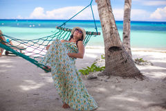 Young woman lying in the hammock on tropical beach. Happy young woman lying in the hammock on tropical beach Stock Images