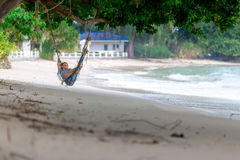 Young woman lying in the hammock on tropical beach. Young woman in striped dress lying in the hammock on tropical beach Royalty Free Stock Photos