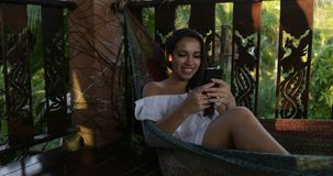 Young Woman Lying In Hammock Use Cell Smart Phone Chatting Online On Summer Terrace. Slow Motion 60 stock video footage