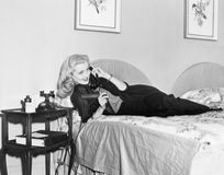 Young woman lying on her bed in the bedroom and talking on the telephone Royalty Free Stock Images