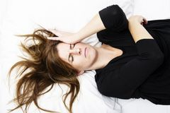 Young woman is lying in her bed with a painful expression on her face. Healthcare concept stock images