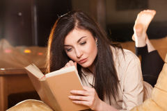 Young woman lying on her couch reading a book at home Stock Image