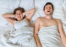 Young woman is lying with her husband in bed. Man is snoring too loud. Woman is covering her ears Royalty Free Stock Images