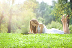 Young Woman Lying with Laptop on the Beautiful Green Meadow royalty free stock photography