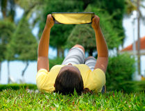Young woman lying on the lawn with a tablet computer Royalty Free Stock Photos