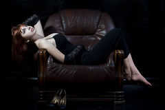 Young woman lying on the leather chair Royalty Free Stock Photography