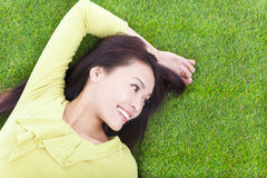 Young woman lying and looking side in a meadow Stock Images