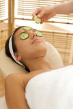 Young woman lying on massage table with cucumber slice being placed over eye Royalty Free Stock Photography