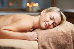 Young woman lying on massage table in spa Royalty Free Stock Photos