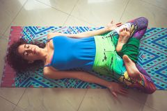 Young woman lying on mat with legs in lotus position indoor shot Stock Photo