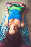 Young woman lying on mat with legs in lotus position indoor shot Stock Photography