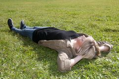 Young woman lying on a meadow Stock Photos