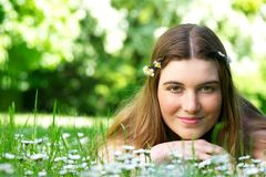 Young woman lying in meadow with flowers Stock Photography
