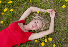 Young woman lying on a meadow Stock Photography