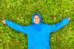 Young woman lying on a meadow. Young woman in a rain jacket lying on grass royalty free stock image