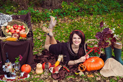 Young woman lying near the vegetables in the autumn park. Smiling pretty young woman lying on the foliage near the vegetables in the autumn park stock photography