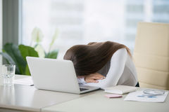 Young woman lying at the office desk near laptop Stock Images