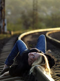 Young Woman Lying On Rail Stock Photography