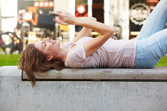 Young woman lying outdoors and using mobile phone Stock Images