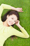 Young woman lying in the park meadow Royalty Free Stock Image