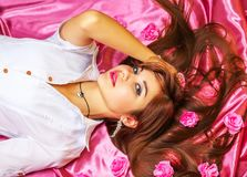 Young woman lying on pink background with flowers. Royalty Free Stock Photography