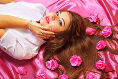 Young woman lying on pink background with flowers. Royalty Free Stock Image