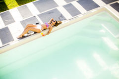 Young woman lying by the pool on sunbed. At ot summer day Royalty Free Stock Photos