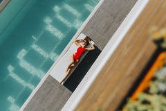 Young woman lying by the pool on sunbed. At ot summer day Royalty Free Stock Image