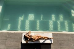 Young woman lying by the pool on sunbed Royalty Free Stock Image