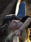 Young woman lying on rail Royalty Free Stock Photography
