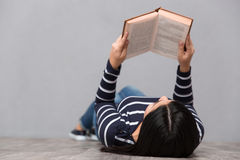 Young woman lying and reading a book Royalty Free Stock Photos