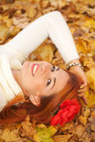 Young woman lying among red leaves. Red-haired young woman lying among red leaves in autumn forest. Outdoor portrait stock image