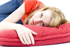 Young woman lying on the red pillow Stock Photography