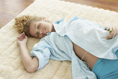 Young Woman Lying On Rug Listening To Music Royalty Free Stock Photo