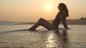 Young woman lying on sand beach and washing by ocean waves. Cute girl relaxing on tropical sea shore at sunset time stock footage