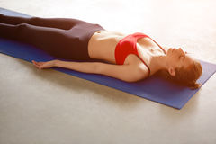 Young woman lying in Shavasana, meditating and breathing. Attractive young woman working out at home, doing yoga exercise on blue mat, lying in Shavasana Stock Photo