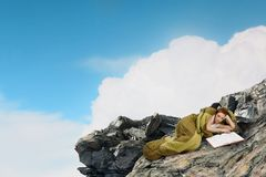 Girl tourist having rest. Mixed media. Young woman lying in sleeping bag on rock edge. Mixed media Royalty Free Stock Photography