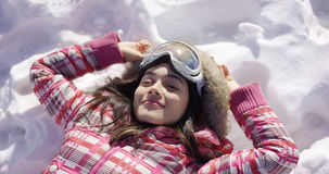 Young woman lying on snow with ski goggles Stock Photography